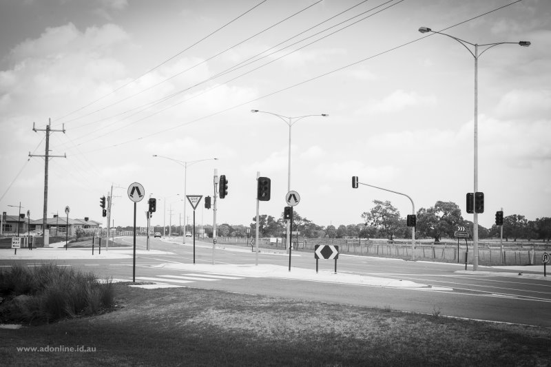New intersection; poles, wires, traffic lights, signs.