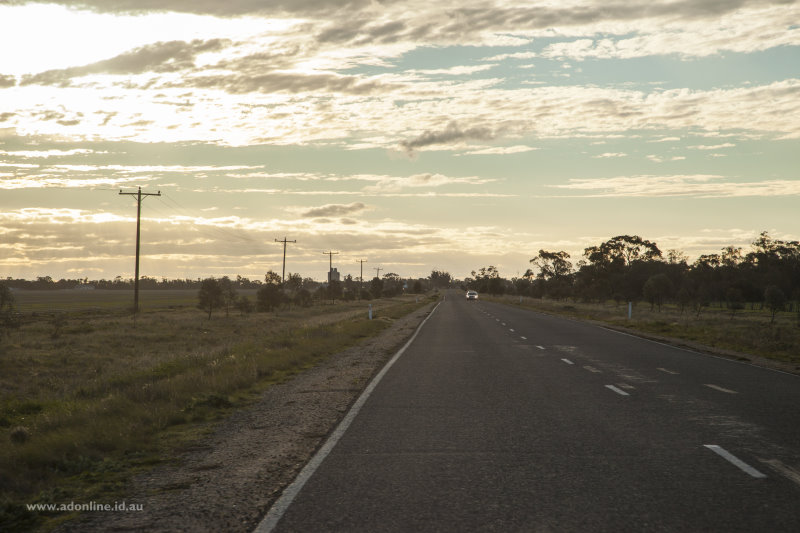 View along highway with clouds obscuring the setting sun.