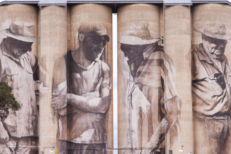 Side of two silos with people painted on their walls.