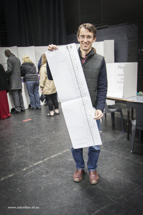 Adam Dimech standing with the Senate ballot paper for Victoria showing its length.
