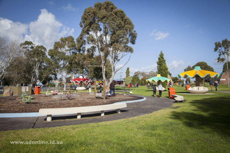 View of gardens with play equipment and tables.