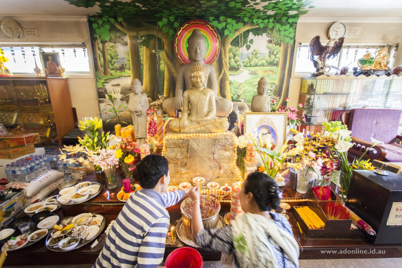 Making prayers in front of statues of Buddha.