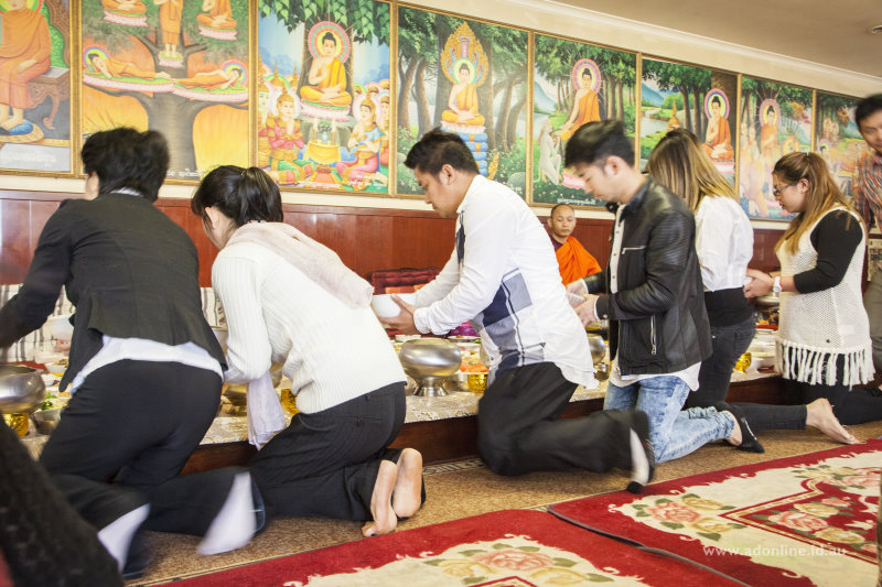 Rice being served into bowls at the front of the altar.