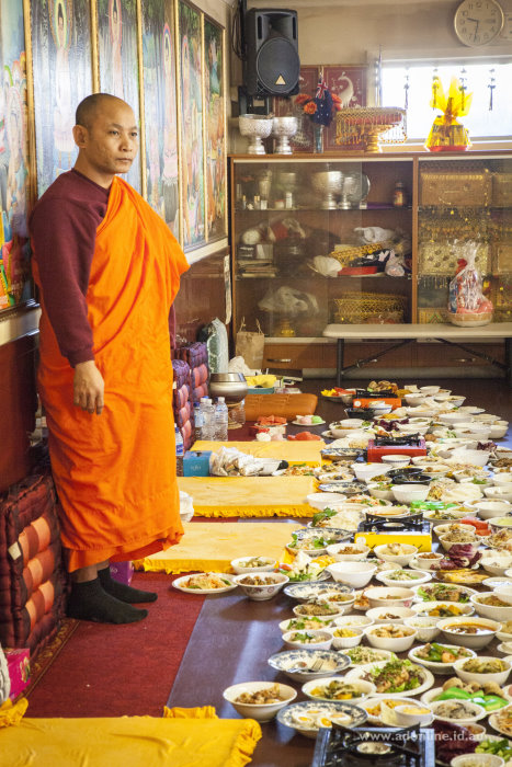 A Buddhist monk overlooking the festivities with the food offerings at his feet.