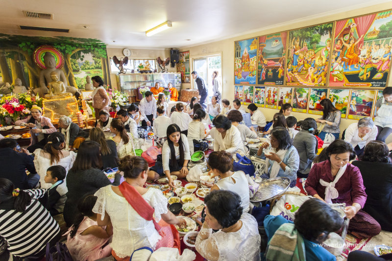 Families eating meals on the floor of the temple.
