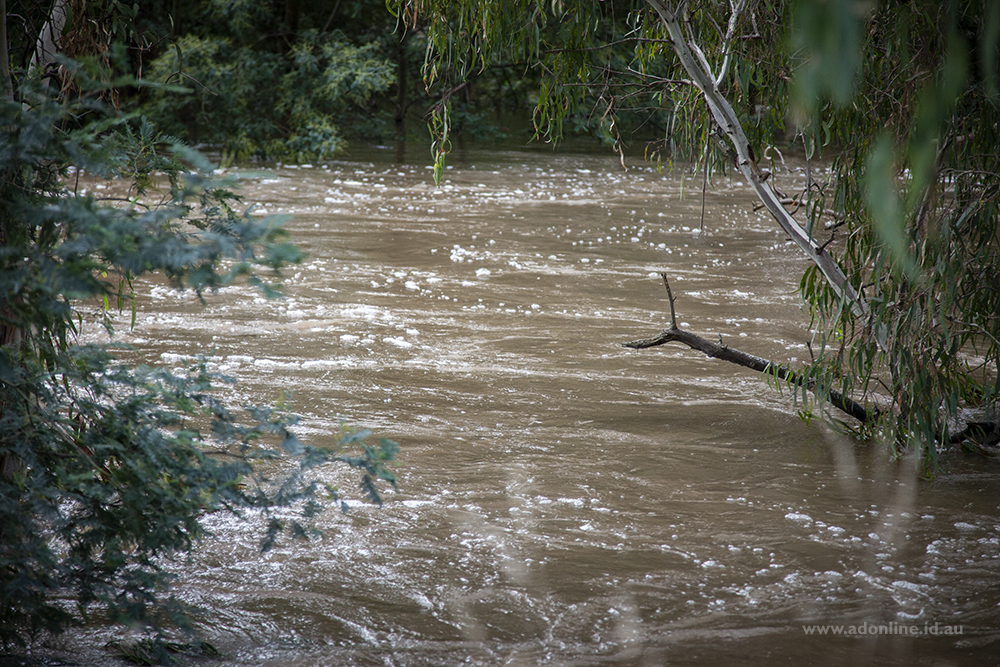 Muddy water flowing down a swollen river.