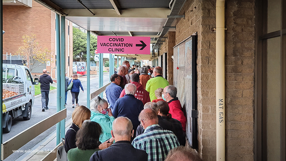 """People queuing beneath a """"Covid Vaccination Clinic"""" sign"""