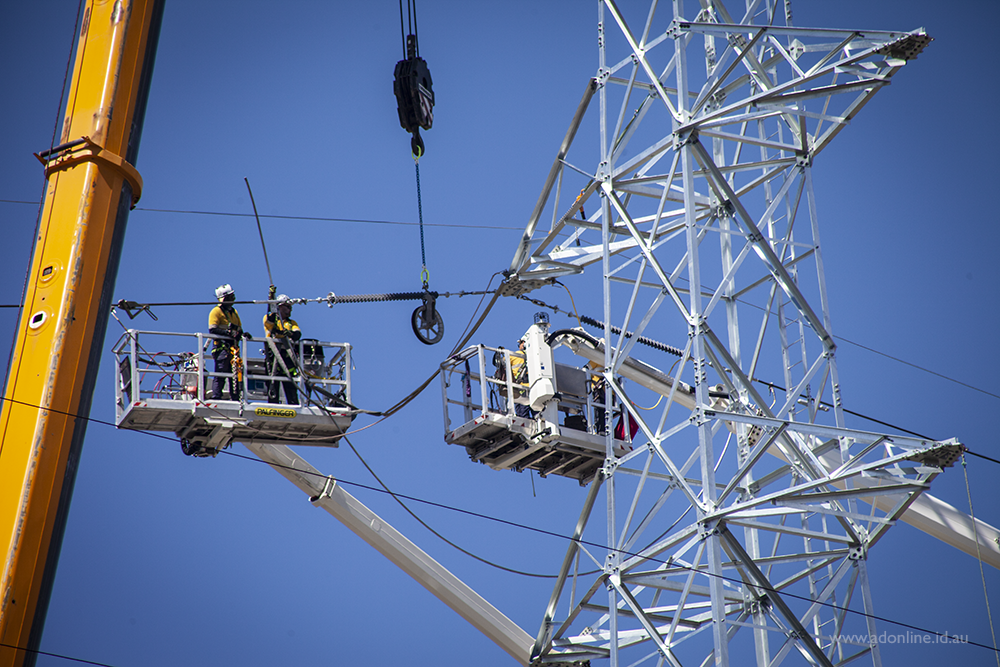 Men atop a cherry picker attaching wires to a pylon with the use of a crane