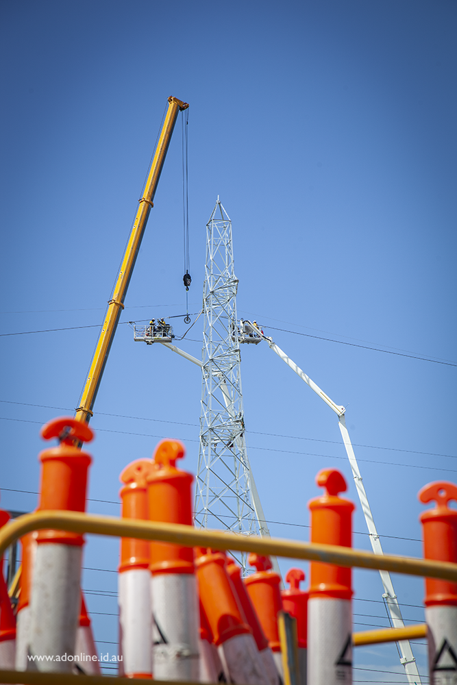 View of transmission tower with men working on it, with a stack of witches hats (safety cones) in the foreground.