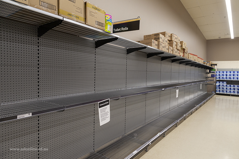 Empty shelves in a supermarket where toilet paper should be.