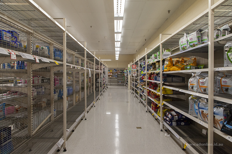 View down supermarket aisle showing empty shelves on left.