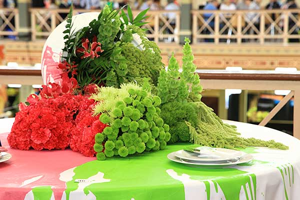 Flowers in green and pink with green and pink paint spilled on the table below them to match.