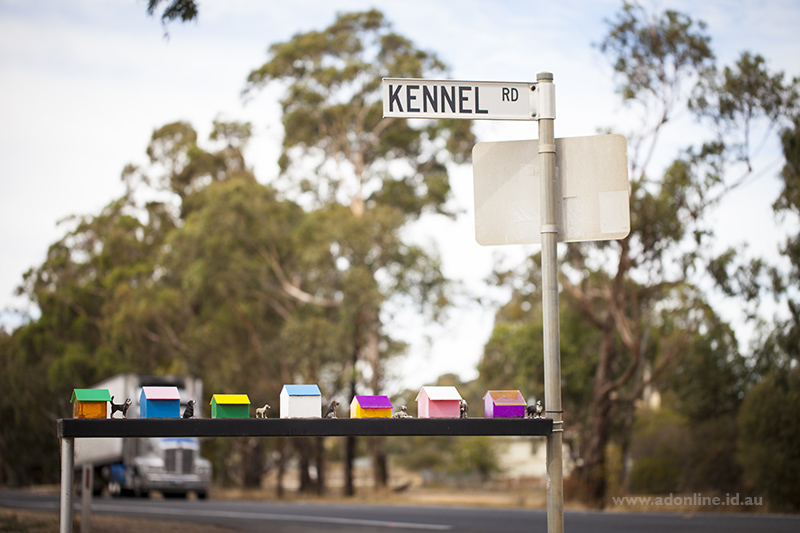 "Street sign that reads ""Kennel Road"" with dog sculpture attached."