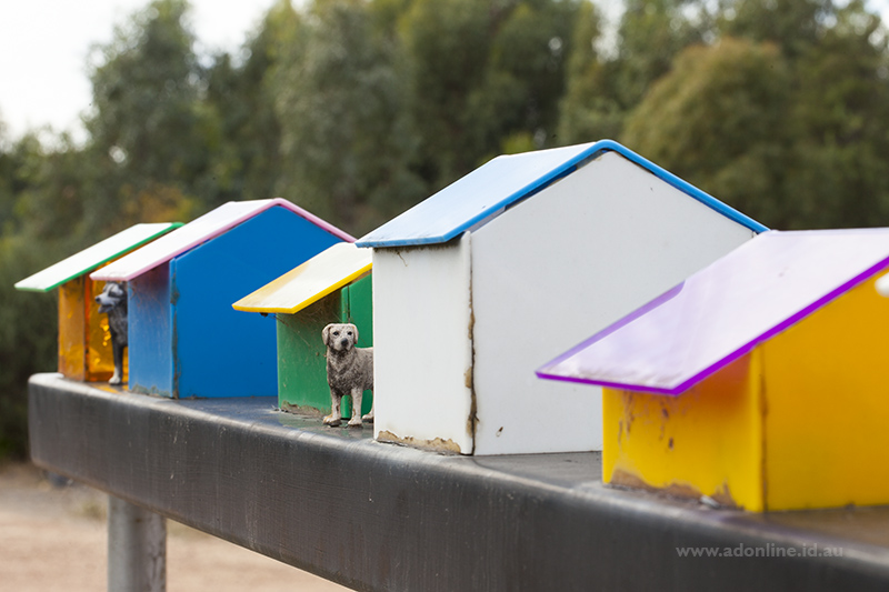 Sculpture of a row of kennels with dog beside.