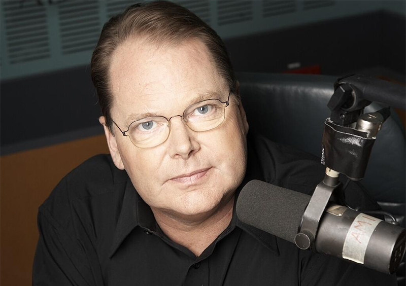 Portrait of Mark Colvin behind a radio microphone.