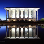 National Library reflected in pond at night.