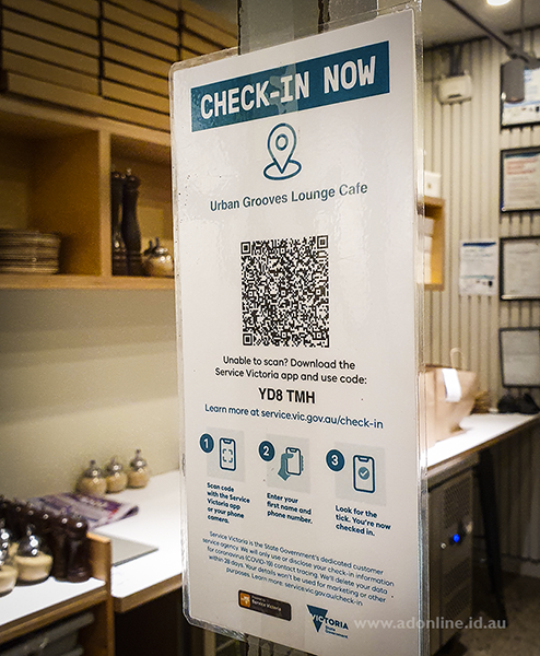 A poster displayed in a shop with a QR code printed on it.