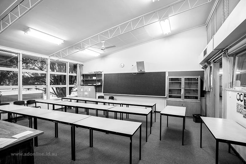 Interior of classroom showing blackboard and tables and chairs.