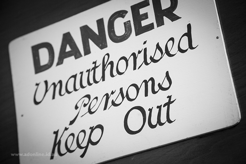 """A hand-painted sign which reads """"Danger. Unauthorised persons keep out"""""""