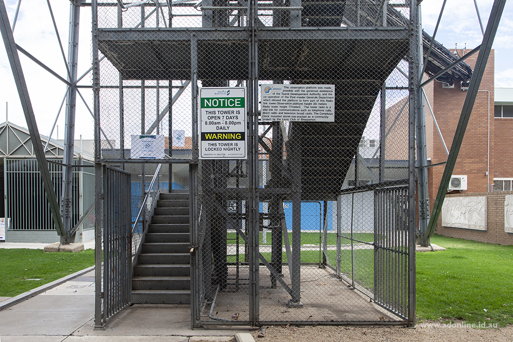 A gate and signage at the base of a telecommunications tower.