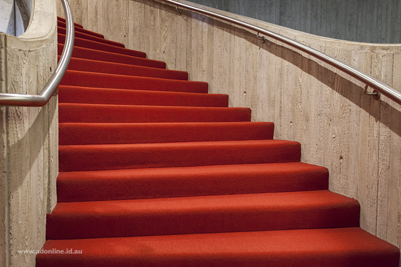 Red carpet on a concrete spiral staircase.