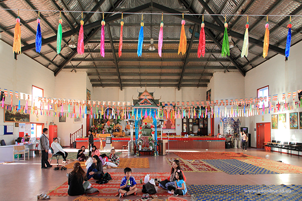 Interior of a buddhist temple with people sitting and eating inside.