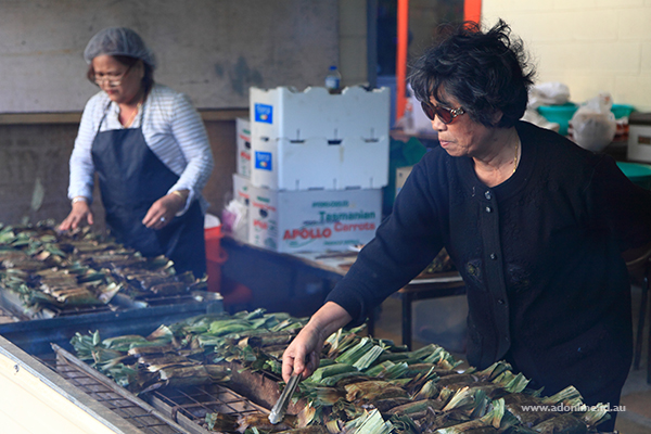 So much smoke! Ladies cooking sticky rice meals wrapped in banana leaves.